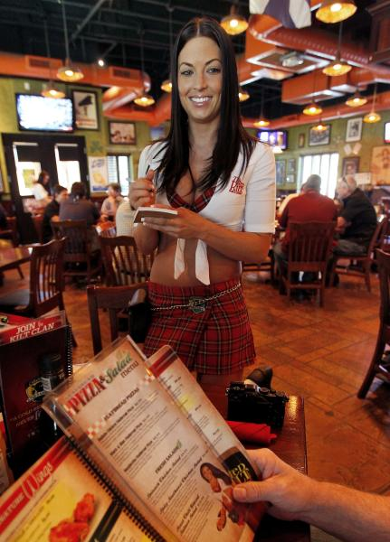 "In this May 16, 2012 photo, Ashley Carpenter takes lunch orders at the Tilted Kilt, in Tempe, Ariz. The Tilted Kilt is part of a booming niche in the beleaguered restaurant industry known as ""breastaurants,"" or sports bars that feature scantily-clad waitresses. These small chains operate in the tradition of Hooters, which pioneered the concept in the 1980s but has struggled in recent years to stay fresh. (AP Photo/Matt York)"