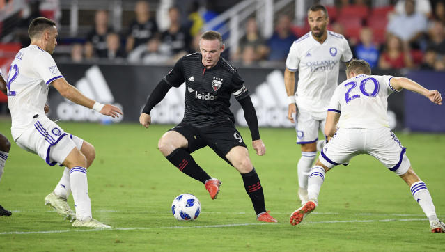 FILE - In this file photo dated Sunday, Aug. 12, 2018, D.C. United forward Wayne Rooney (9) dribbles the ball against Orlando City midfielder Oriol Rosell (20) and defender Shane O'Neill, left, during the first half of an MLS soccer match, in Washington, USA. It is announced Tuesday Aug. 6, 2019, that 33-year old former England captain Wayne Rooney will be leaving US Major League Soccer to join second-tier English Championship team Derby County as player-coach from January 2020.(AP Photo/Nick Wass, FILE)