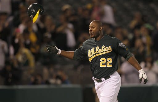 Oakland Athletics ' Chris Carter (22) tosses his helmet after hitting a three-run home run during the eleventh inning of a baseball game against the Seattle Mariners in Oakland, Calif., Friday, July 6, 2012. The Athletics won 4-1 in 11 innings. (AP Photo/Jeff Chiu)