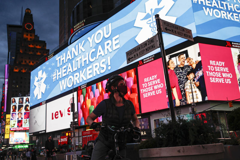 "A screen displaying a messages thanking healthcare workers due to COVID-19 concerns is displayed in a sparsely populated Times Square, Friday, March 20, 2020, in New York. New York Gov. Andrew Cuomo is ordering all workers in non-essential businesses to stay home and banning gatherings statewide. ""Only essential businesses can have workers commuting to the job or on the job,"" Cuomo said of an executive order he will sign Friday. Nonessential gatherings of individuals of any size or for any reason are canceled or postponed. (AP Photo/John Minchillo)"