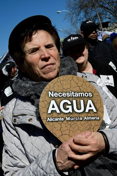 """A woman holds a placard reading """"We need water in Alicante, Murcia and Almeria"""" at a protest in Madrid by thousands of farmers from Spain's parched southeast"""