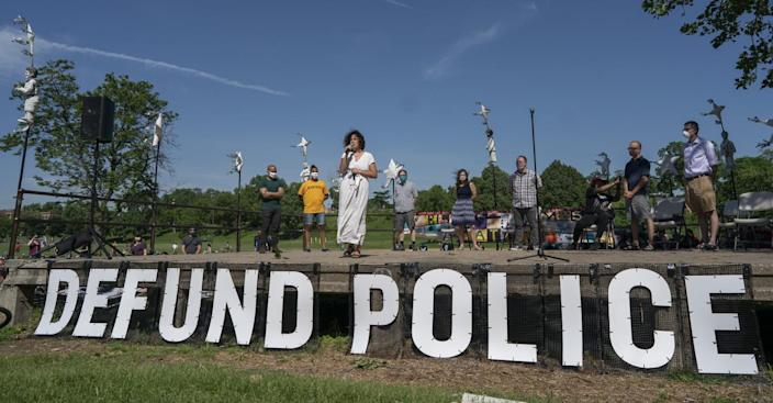 "A speaker stands before a ""Defund Police"" sign"
