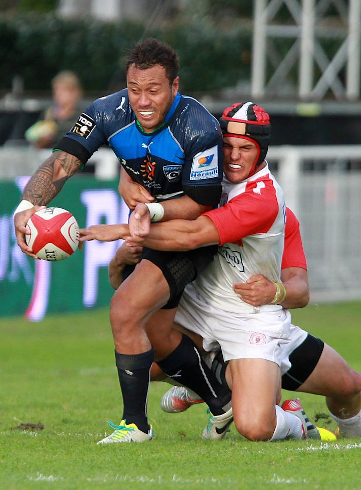 Montpellier's Anthony Tuitavake, left, is tackled by Biarritz's Daniel Waenga during their French Top 14 rugby union match at the Stade Aguilera, in Biarritz, southwestern France, Saturday Aug. 24, 2013. (AP Photo/Bob Edme)