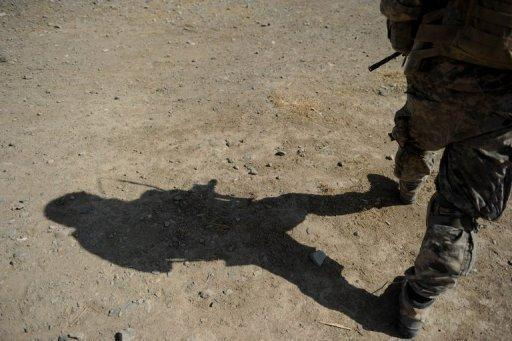 A US soldier patrols a village in Kandahar province, southern Afghanistan in 2010. The White House and NATO on Wednesday condemned grisly photographs showing US soldiers with the mangled remains of suspected Taliban suicide bombers in Afghanistan