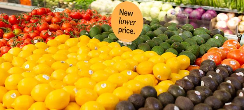 "A produce stand with a sign that says ""New lower price."""