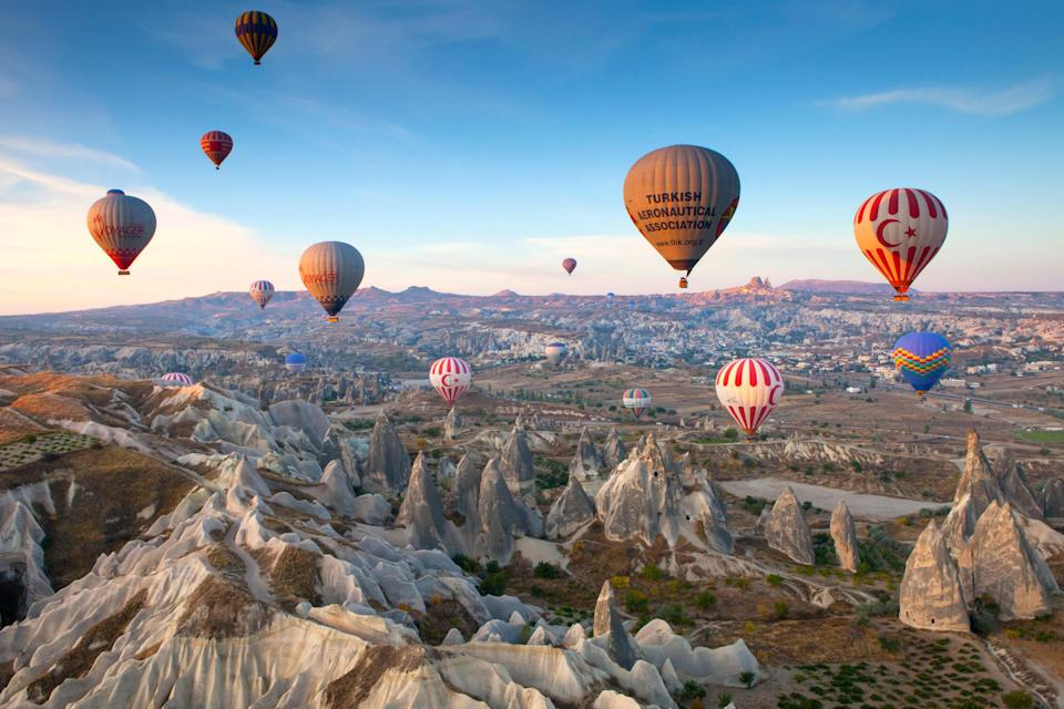 """A hot air balloon ride over central Turkey's Cappadocia region is an <a href=""""https://www.cntraveler.com/gallery/adventures-to-have-in-a-lifetime?mbid=synd_yahoo_rss"""" rel=""""nofollow noopener"""" target=""""_blank"""" data-ylk=""""slk:adventure"""" class=""""link rapid-noclick-resp"""">adventure</a> every traveler should experience—especially if you plan your trip right after the scorching hot summer months. The sky-high ride provides 360-degree views of the famous limestone spires and """"fairy chimneys""""—something you can't get at the ground level. We recommend booking with <a href=""""http://kapadokyaballoons.com/en/index.html"""" rel=""""nofollow noopener"""" target=""""_blank"""" data-ylk=""""slk:Kapadokya Balloons"""" class=""""link rapid-noclick-resp"""">Kapadokya Balloons</a>, the first company that introduced hot air balloon tourism in Cappadocia. Services include transfers to and from your hotel, snacks, full insurance, and a champagne party after the flight. Speaking of hotels, head to the tony town of Ürgüp (about a 45-minute drive from Cappadocia) and book a room at <a href=""""https://www.esbelli.com/"""" rel=""""nofollow noopener"""" target=""""_blank"""" data-ylk=""""slk:Esbelli Evi"""" class=""""link rapid-noclick-resp"""">Esbelli Evi</a>, a 10-room hillside hotel carved into the rock. Accommodations are undeniably cavelike, with sloping walls and rounded ceilings, but the atmosphere is high-end—think antique writing desks and claw-foot tubs. (As of now, unvaccinated tourists must provide a negative PCR test within 72 hours of arrival.)"""