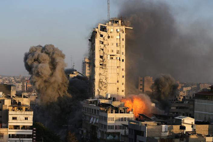 <p>Smoke and flames rise from a tower building as it is destroyed by Israeli airstrikes in Gaza City</p> (Reuters)