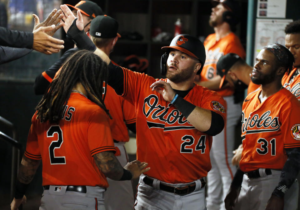 Baltimore Orioles' DJ Stewart is greeted in the dugout by teammates after scoring on an RBI single by Trey Mancini against the Texas Rangers during the eighth inning of a baseball game in Arlington, Texas, Saturday, April 17, 2021. (AP Photo/Ray Carlin)