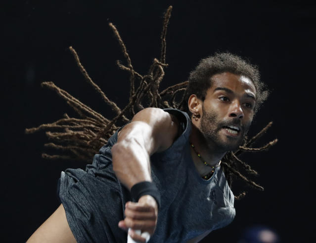 Germany's Dustin Brown serves to Portugal's Joao Sousa during their first round match at the Australian Open tennis championships in Melbourne, Australia, Monday, Jan. 15, 2018. (AP Photo/Ng Han Guan)