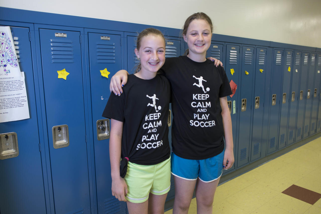 In this Thursday, June 6, 2013 photo, Nikki Rothstein, left, and her twin sister, Alexandra, one of the 24 sets of twins from Highcrest Middle School in Wilmette, Ill., pose for a portrait at the school. The group is attempting to break a Guinness World record for the amount of twins in one grade which is currently s16 sets. (AP Photo/Scott Eisen)
