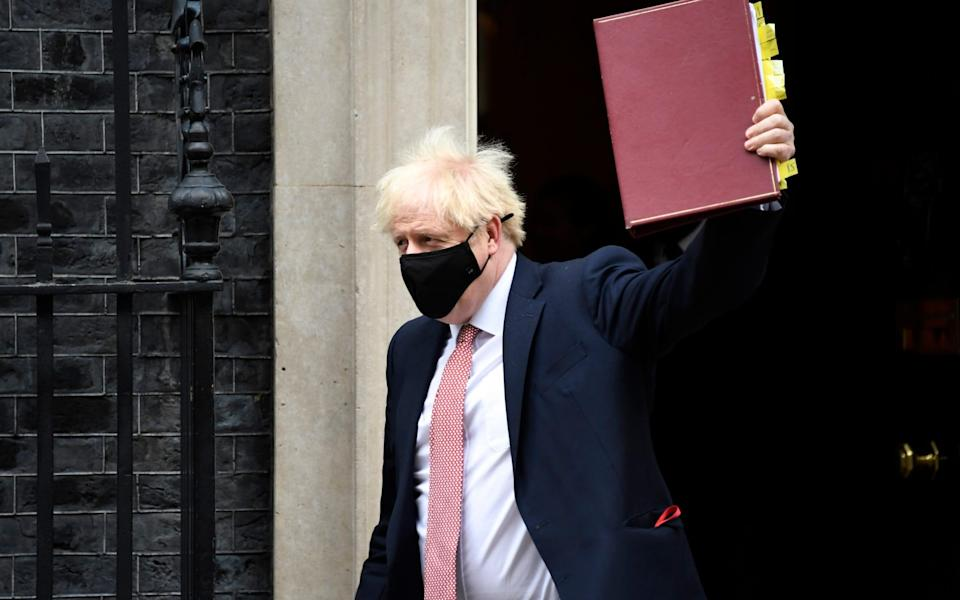 Boris Johnson wears a mask as he leaves 10 Downing Street to attend PMQs - AP