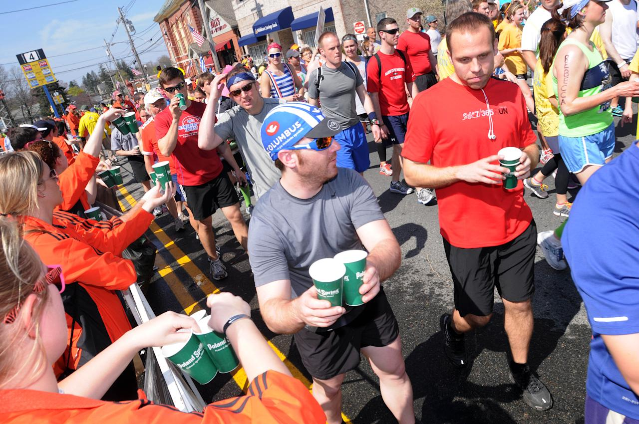 HOPKINTON, MA - APRIL 16: Runners take water from volunteers during the start of the 116th running of the Boston Marathon April 16, 2012 in Hopkinton, Massachusetts. (Photo by Darren McCollester/Getty Images)