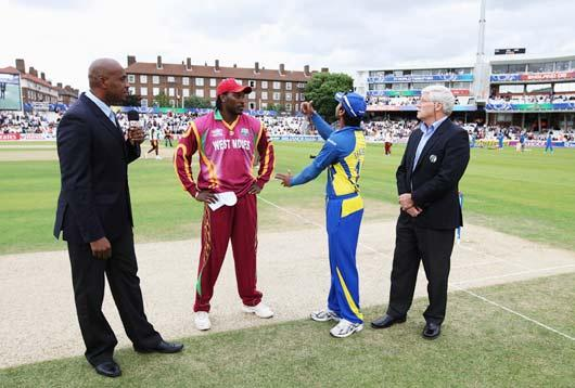 Kumar Sangakkara of Sri Lanka tosses the coin watched by Chris Gayle of West Indies, commentator Ian Bishop and match referee Alan Hurst during the ICC World Twenty20 Semi Final between Sri Lanka and West Indies at the Brit Oval. (Getty Images)