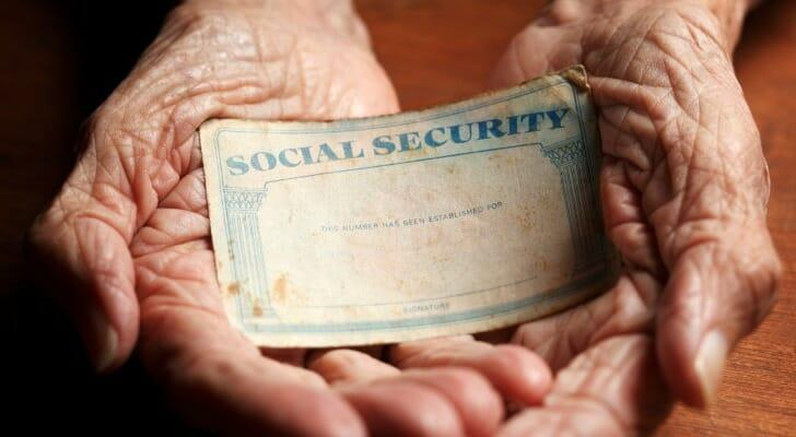Elderly person's hands holding a Social Security card