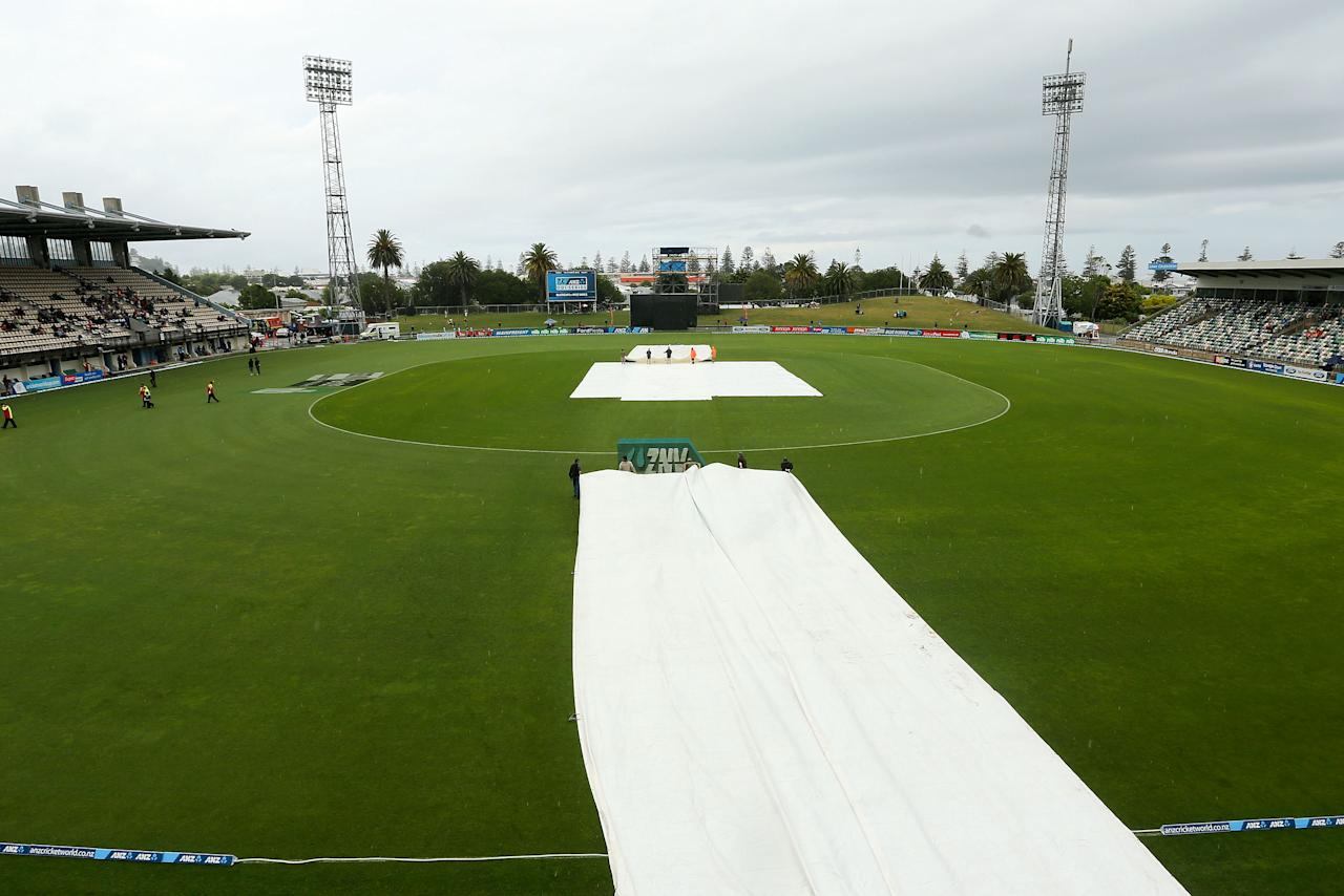NAPIER, NEW ZEALAND - DECEMBER 29:  Covers are moved onto the wicket during a rain delay prior to game two of the One Day International series between New Zealand and the West Indies at McLean Park on December 29, 2013 in Napier, New Zealand.  (Photo by Hagen Hopkins/Getty Images)