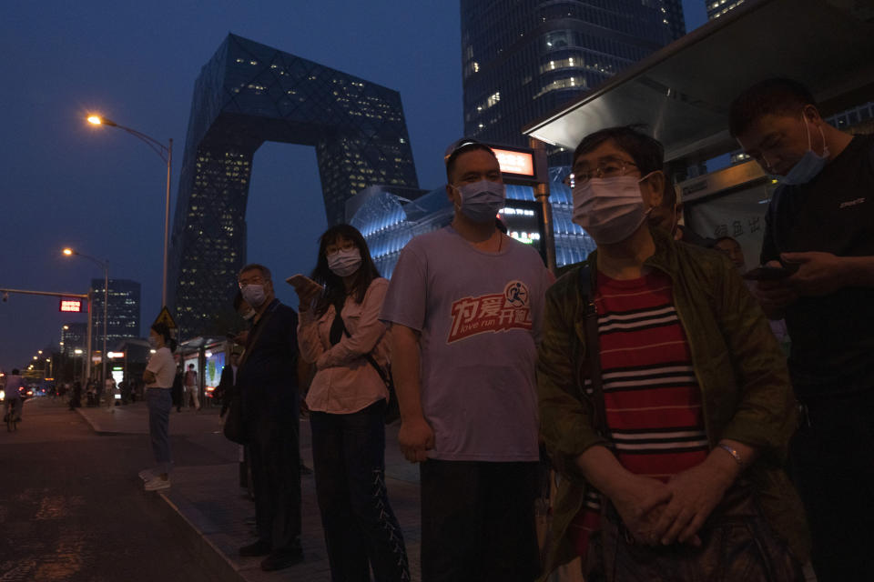 """Residents wearing masks wait at a bus stop in Beijing Saturday, Sept. 18, 2021. China's """"zero tolerance"""" strategy of trying to isolate every case and stop transmission of the coronavirus has kept kept the country where the virus first was detected in late 2019 largely free of the disease. (AP Photo/Ng Han Guan)"""