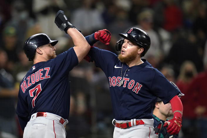Boston Red Sox's Alex Verdugo, right, is greeted at the plate by Christian Vazquez on Verdugo's two-run home run against the Seattle Mariners during the eighth inning of a baseball game Tuesday, Sept. 14, 2021, in Seattle. (AP Photo/Elaine Thompson)