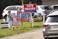 """Volunteers from left, Kim Pinnix, left, and her friend Robyn Agnew, center, wife of justice court judge candidate Bo Agnew, wave at incoming voters, while Jake Williams hoists a """"Tate Reeves for Governor"""" sign outside a Flowood, Miss., precinct, Tuesday, Aug. 27, 2019. Runoff candidates of both parties staffed many precincts statewide as they seek runoff wins. (AP Photo/Rogelio V. Solis)"""