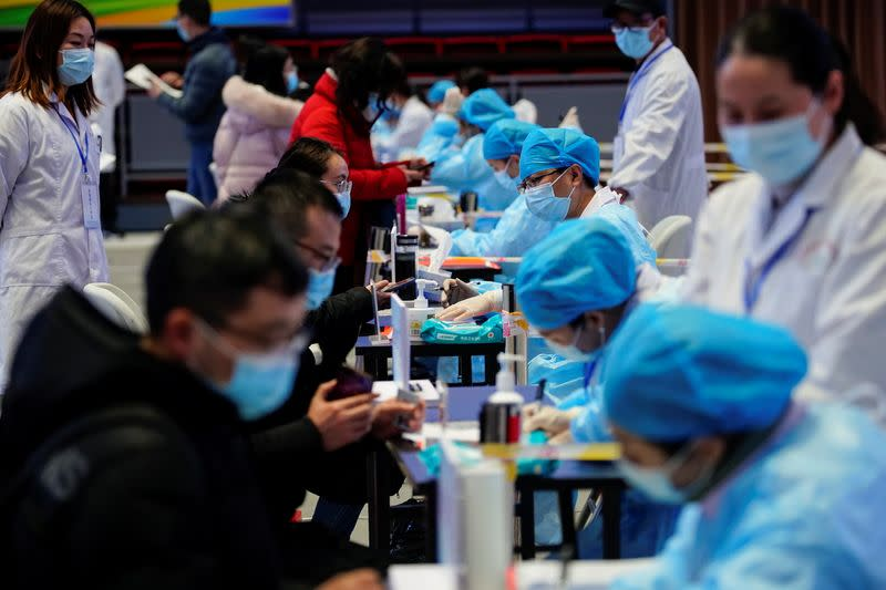 People fill forms before receiving a dose of a coronavirus disease (COVID-19) vaccine at a vaccination site, in Shanghai