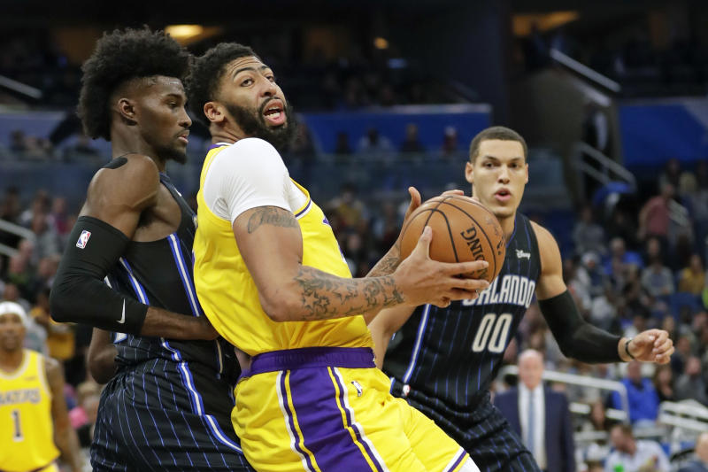 Los Angeles Lakers forward Anthony Davis, center, looks for a way to the basket around Orlando Magic forward Jonathan Isaac, left, and Aaron Gordon (00) during the first half of an NBA basketball game, Wednesday, Dec. 11, 2019, in Orlando, Fla. (AP Photo/John Raoux)