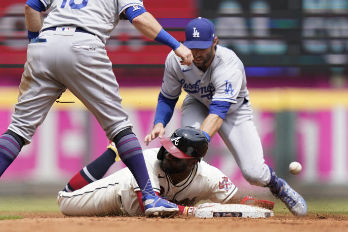 Atlanta Braves' Abraham Almonte, bottom, advances to second base as the ball gets away from Los Angeles Dodgers left fielder Chris Taylor, top right, after a Ehire Adrianza base hit in the sixth inning of a baseball game Sunday, June 6, 2021, in Atlanta. (AP Photo/Brynn Anderson)