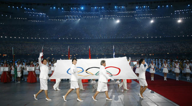 The Olympic flag is carried through National Stadium during the opening ceremonies for the Beijing 2008 Olympics in Beijing, Friday, Aug. 8, 2008. (AP Photo/Kevin Frayer)