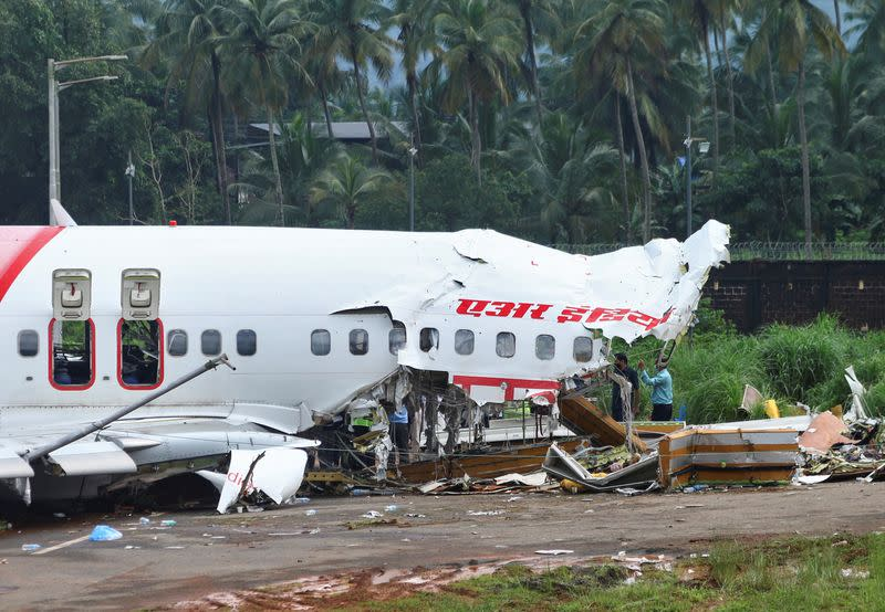 Officials inspect the site where a passenger plane crashed when it overshot the runway at the Calicut International Airport in Karipur