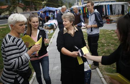 Volunteers hand out leaflets with information about new Bosnia's census in Jablanica, 60 kilometres (37 miles) south of Sarajevo, September 27, 2013. REUTERS/Dado Ruvic