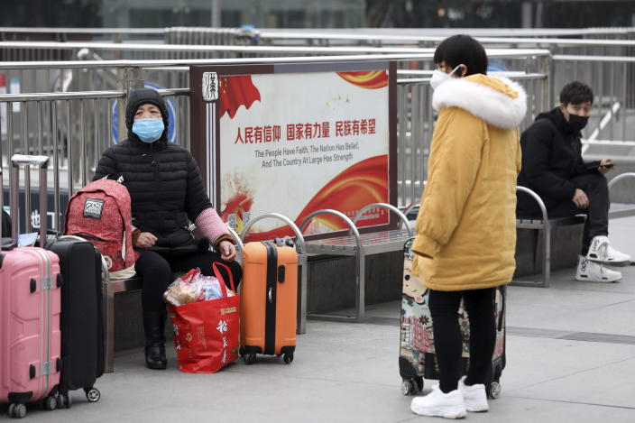 FILE - In this Jan. 23, 2020, file photo, travelers sit with their luggage outside the closed Hankou Railway Station in Wuhan in central China's Hubei Province. The Chinese city of Wuhan is looking back on a year since it was placed under a 76-day lockdown beginning Jan. 23, 2020. (Chinatopix via AP, File)