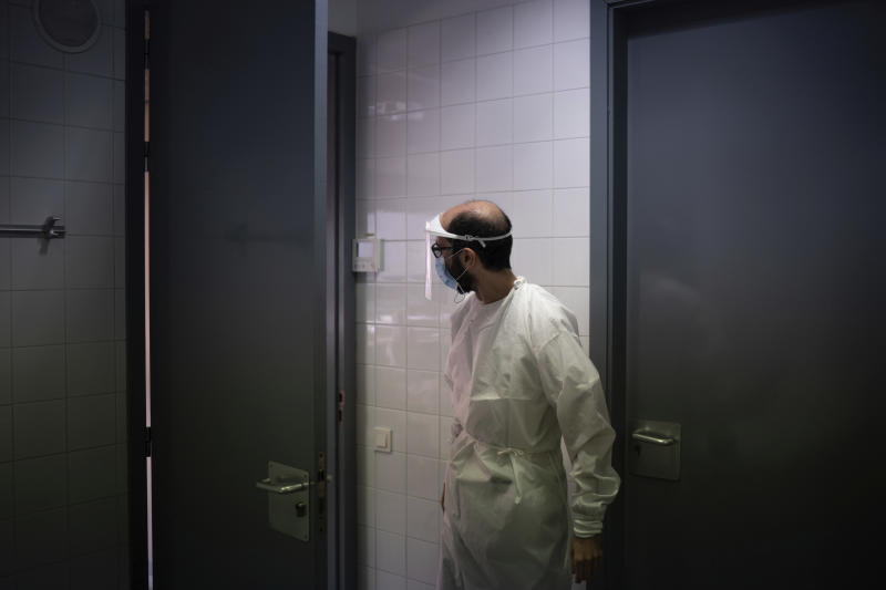 In this July 31, 2020 file photo, a health worker waits for a patient to be tested for COVID-19 at a Primary Health Care Center in Sant Sadurní d'Anoia, Catalonia region, Spain. Spain's improved testing capacity makes a comparison to the start of the pandemic difficult. In February, March and April, a shortage of tests meant that only the very sick who were admitted to hospitals were tested and that a significant number of coronavirus cases went undetected. (AP Photo/Felipe Dana)