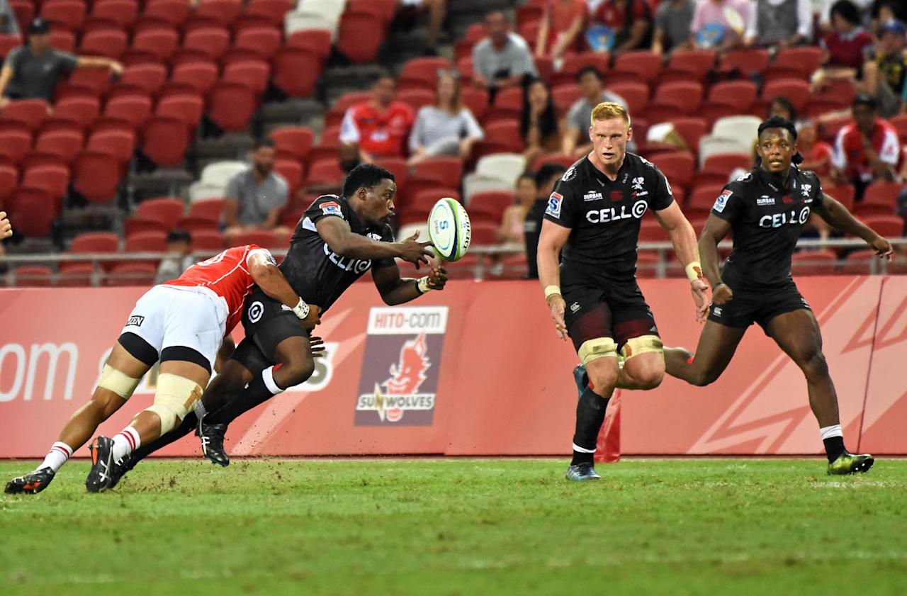 Lwazi Mvovo of Sharks (2L) is tackled by Rahboni Warren-Vosayaco of Sunwolves as he passes the ball during the Super Rugby match between Japan's Sunwolves and South Africa's Sharks in Singapore on May 20, 2017. (AFP Photo/ROSLAN RAHMAN)