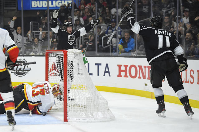 Los Angeles Kings right wing Tyler Toffoli, rear, celebrates with center Anze Kopitar, right, after Toffoli scored on Calgary Flames goaltender David Rittich during the second period of an NHL hockey game Wednesday, Feb. 12, 2020, in Los Angeles. (AP Photo/Mark J. Terrill)