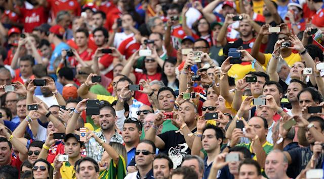 Spectators take photos as the teams line up before the group B World Cup soccer match between Spain and Chile at the Maracana Stadium in Rio de Janeiro, Brazil, Wednesday, June 18, 2014