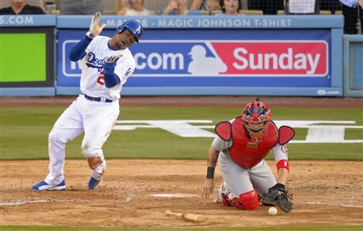 Los Angeles Dodgers' Carl Crawford, left, reacts after scoring on a double by Mark Ellis as St. Louis Cardinals catcher Yadier Molina, right, takes a late throw during the sixth inning of their baseball game on Saturday, May 25, 2013, in Los Angeles. (AP Photo/Mark J. Terrill)