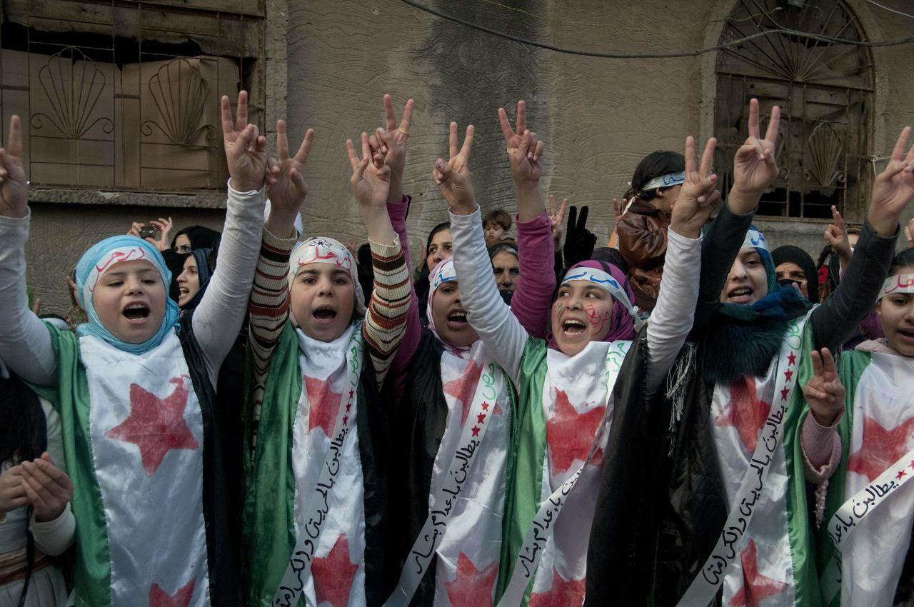 """FILE - In this Dec. 21, 2011 file photo, anti-Syrian regime protesters flash the victory sign as they wear Syrian revolution flags during a demonstration in the Baba Amr area, in Homs province, Syria. The Syria Justice and Accountability Center, a Washington-based Syrian rights group said in a report, released Tuesday, May 21, 2019, that thousands of documents collected from abandoned Syrian government offices reveal the reach of President Bashar Assad's security agencies, offering a rare glimpse into the inner workings of his secretive apparatus. The documents include handwritten notes from top commanders to """"do what is necessary"""" to quell anti-Assad protests. (AP Photo, File)"""