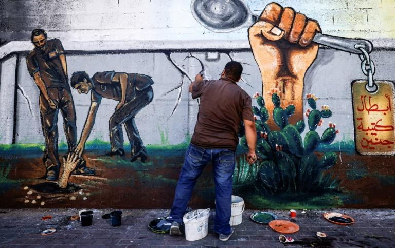An artist in Gaza City works on a mural glorifying six Palestinians who escaped from Israel's Gilboa prison by using a spoon and other tools to dig a tunnel (AFP/MAHMUD HAMS)