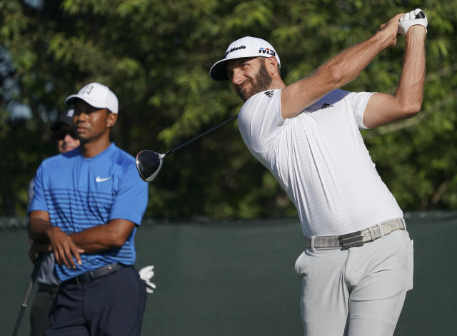 Dustin Johnson hits off the fourth tee as Tiger Woods looks on during a practice round for the U.S. Open Golf Championship, Tuesday, June 12, 2018, in Southampton, N.Y. (AP Photo/Carolyn Kaster)