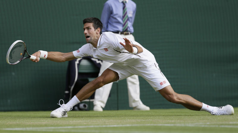 Novak Djokovic of Serbia stretches for the ball as he plays Tommy Haas of Germany during a Men's singles match at the All England Lawn Tennis Championships in Wimbledon, London, Monday, July 1, 2013. (AP Photo/Alastair Grant)