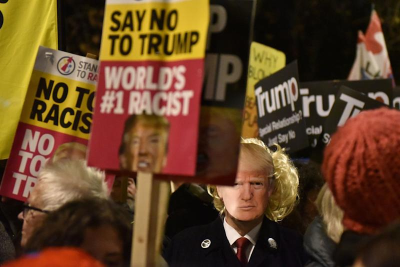"Anti Trump protesters hold ""Say No To Trump and World's #1 Racist"" placards as NATO leaders attend Buckingham Palace on December 3. Source: John Keeble/Getty Images"