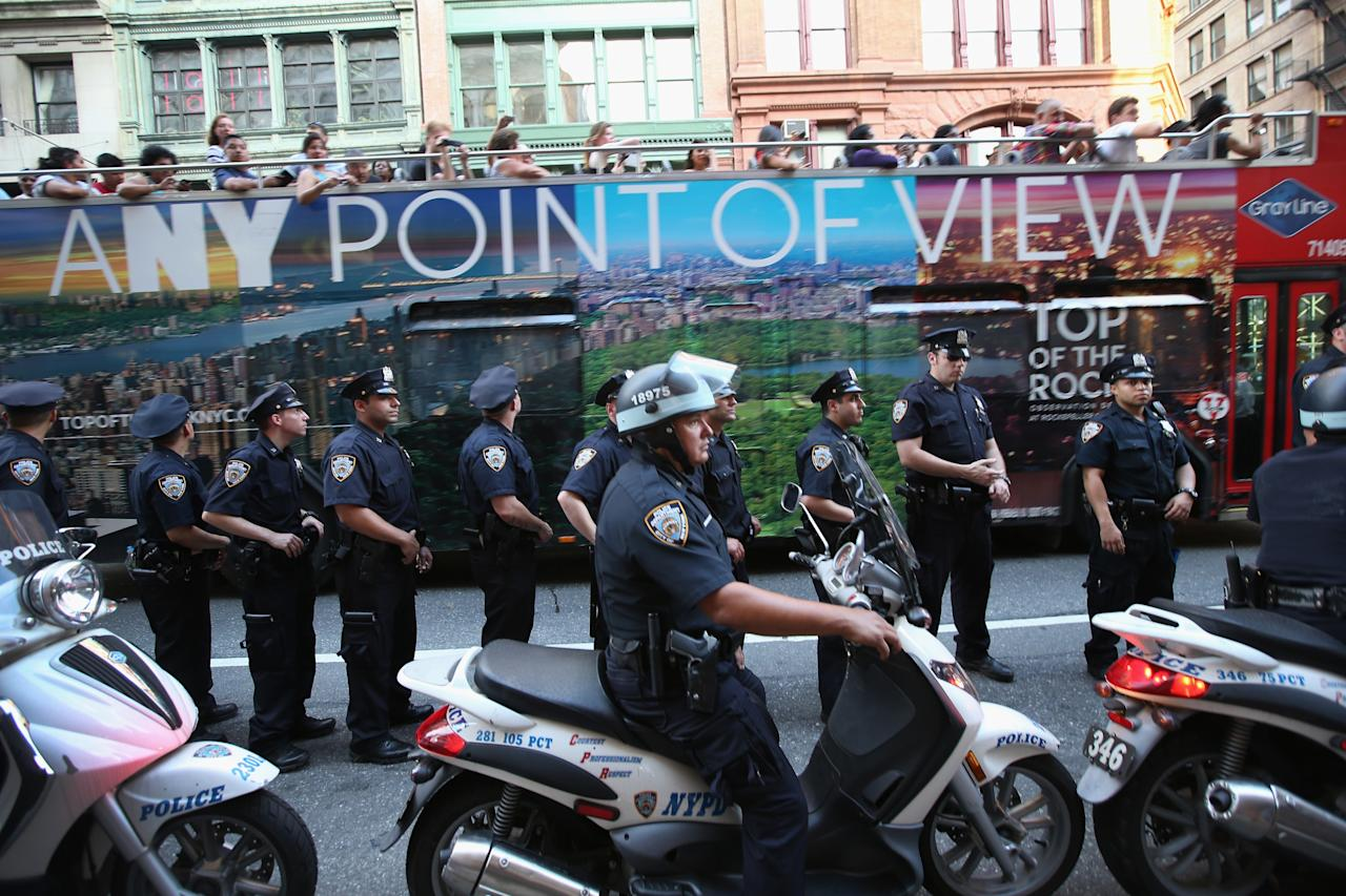 NEW YORK, NY - JULY 15: A tour bus passes police who were monitoring a protest march of Trayvon Martin supporters on July 15, 2013 in New York City. George Zimmerman was acquitted of all charges in the shooting death of Martin July 13 and many protesters questioned the verdict. (Photo by John Moore/Getty Images)