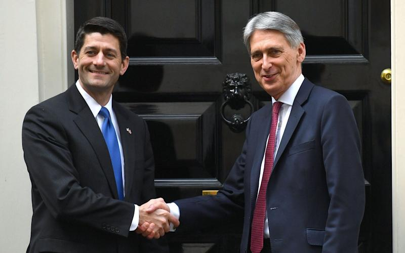 Chancellor Philip Hammond (R) shakes hands with US Speaker of the House of Representatives, Paul Ryan outside No 11, Downing Street - AFP