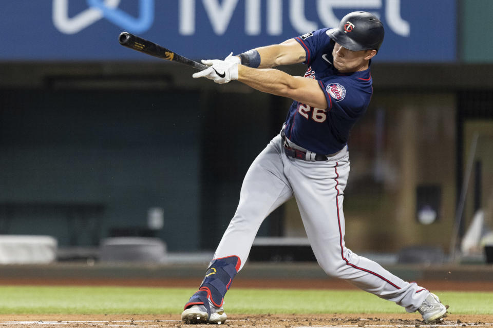 Minnesota Twins' Max Kepler (26) hits a single and drives in a run during the first inning of a baseball game against the Texas Rangers in Arlington, Texas, Friday, June 18, 2021. (AP Photo/Andy Jacobsohn)