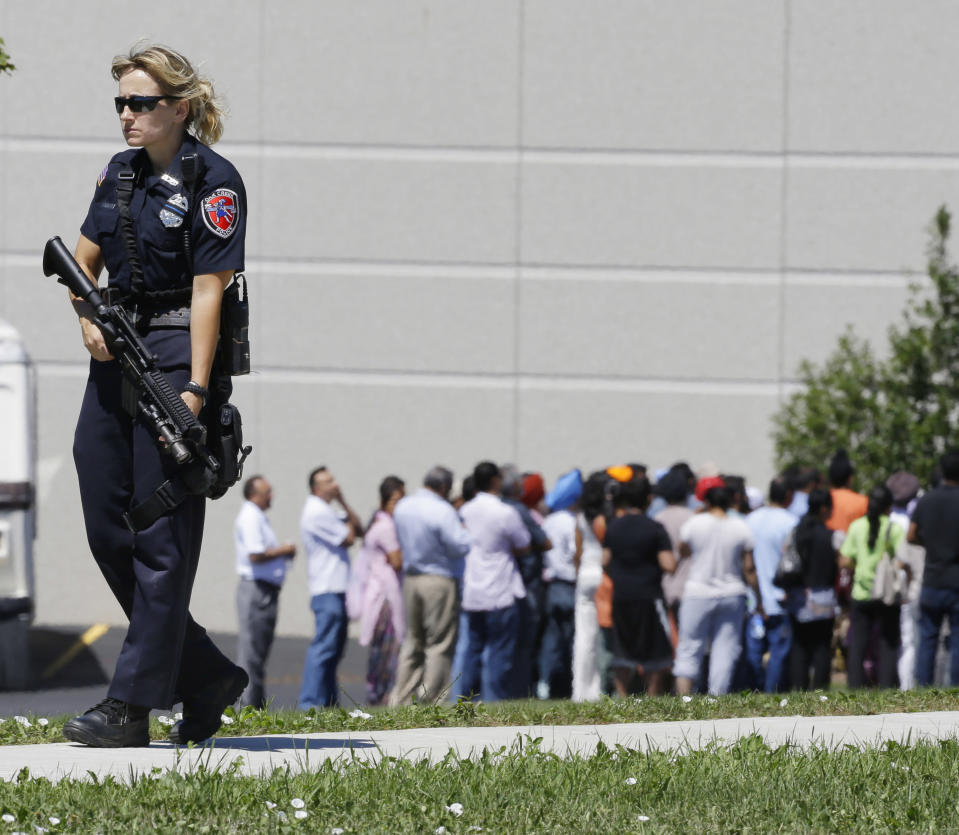 Police stand guard as bystanders watch at the scene of a shooting inside a Sikh temple in Oak Creek, Wis., Sunday, Aug. 5, 2012. Police and witnesses describe a chaotic situation with an unknown number of victims, suspects and possible hostages. (AP Photo/Jeffrey Phelps)