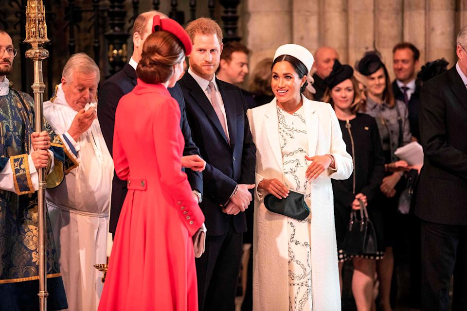 The Duchess of Cambridge (foreground) and Duchess of Sussex greet each other as they attend the Commonwealth Service with other members of the royal family at Westminster Abbey on March 11, 2019. (Photo: RICHARD POHLE via Getty Images)