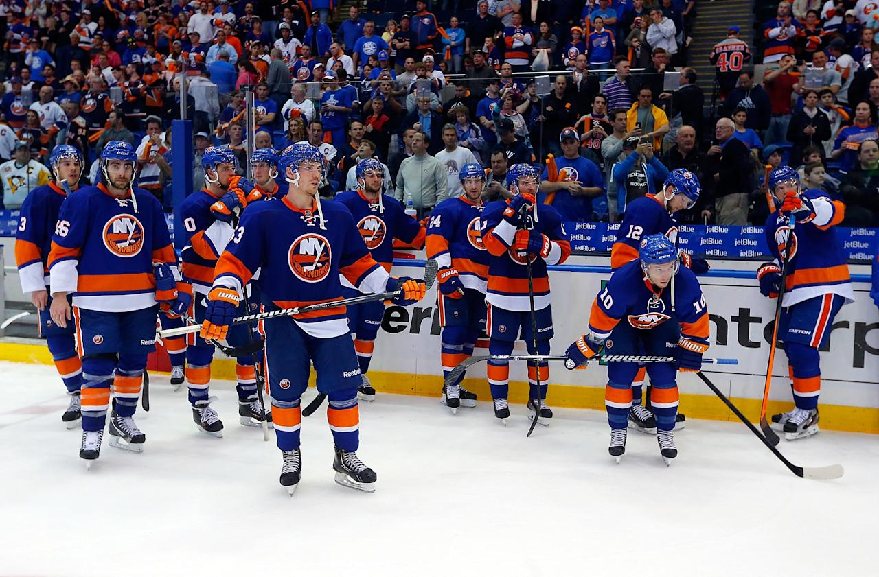UNIONDALE, NY - MAY 11:  New York Islanders stand dejected on the ice as the Pittsburgh Penguins celebrate down the other end of the ice after the Islanders were eliminated from the playoffs in Game Six of the Eastern Conference Quarterfinals  during the 2013 NHL Stanley Cup Playoffs at Nassau Veterans Memorial Coliseum on May 11, 2013 in Uniondale, New York.  Penguins won 4-3 in overtime.  (Photo by Paul Bereswill/Getty Images)