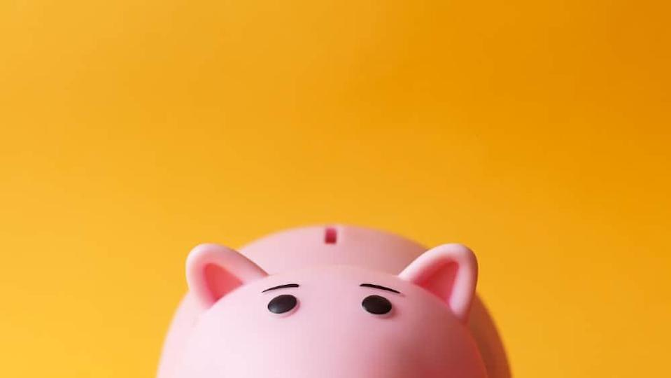 pink toy piggy money box on yellow background