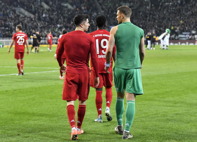 Bayern's goalkeeper Manuel Neuer, right, and Robert Lewandowski leave the pitch disappointed after losing the German Bundesliga soccer match between Borussia Moenchengladbach and Bayern Munich at the Borussia Park in Moenchengladbach, Germany, Saturday, Dec. 7, 2019. Moenchengladbach defeated Bayern with 2-1. Moenchengladbach's Ramy Bensebaini, 3rd from right, scored twice. (AP Photo/Martin Meissner)