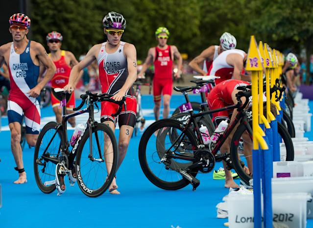 Canada's Kyle Jones runs with his bike in the transition zone as he races in the men's triathlon at Hyde Park during the Summer Olympics in London on Tuesday, August 7, 2012. THE CANADIAN PRESS/Sean Kilpatrick