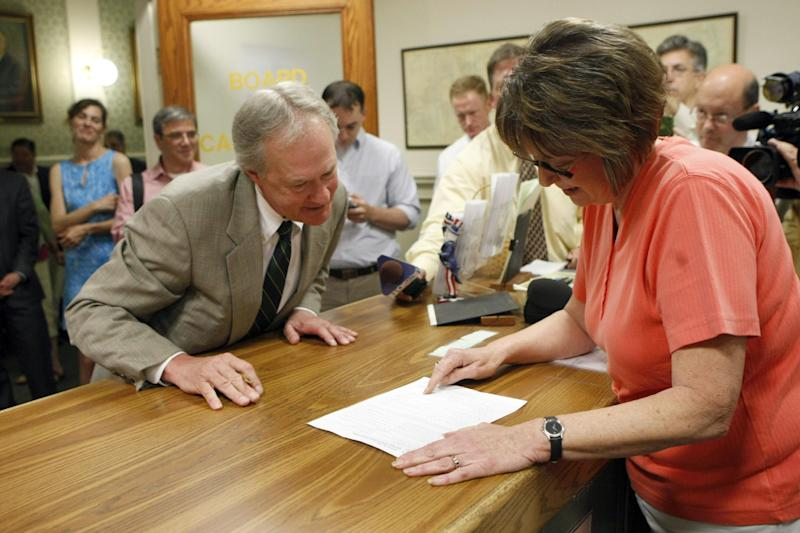 Independent Rhode Island Gov. Lincoln Chafee completes his registration as member of the Democratic Party with Board of Canvassers clerk Dottie McCarthy at City Hall in Warwick, RI on Thursday, May 30, 2013. (AP Photo/Joe Giblin)