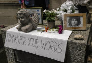 A placard, flowers and pictures are displayed on the tomb of rock singer Jim Morrison at the Pere-Lachaise cemetery in Paris, Saturday, July 3, 2021. Fans across Europe gathered at the grave of rock legend Jim Morrison to mark the 50th anniversary of his death. (AP Photo/Michel Euler)